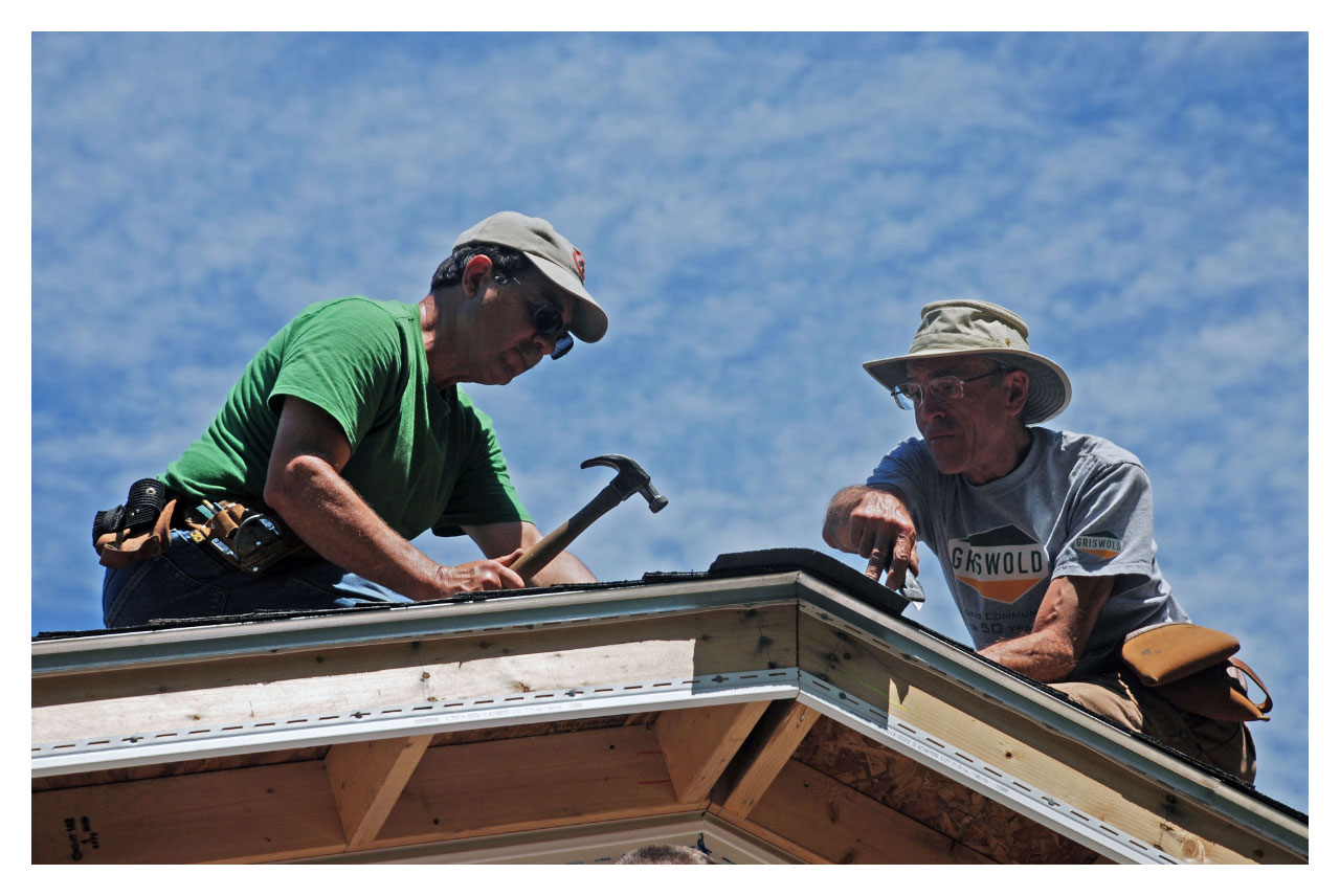 Volunteers attach shingles to a roof on a Green Mountain Habitat for Humanity worksite.