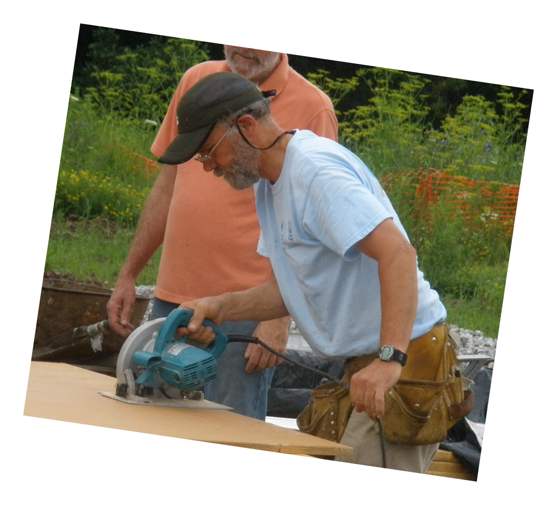 A volunteer uses a circular saw to cut a board on a Green Mountain Habitat for Humanity buildsite