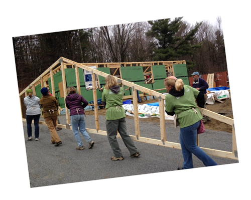 Volunteers carry roof trusses at a Green Mountain Habitat for Humanity buildsite