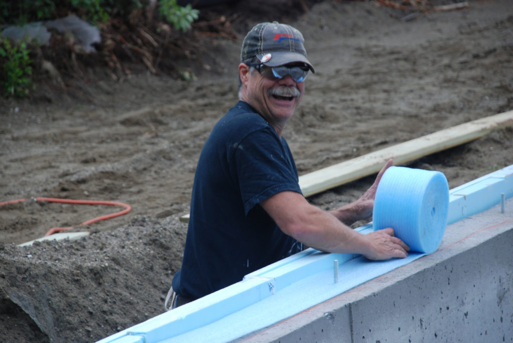 A voluteer rolls out foam insulation at at Green Mountain Habitat for Humanity buildsite