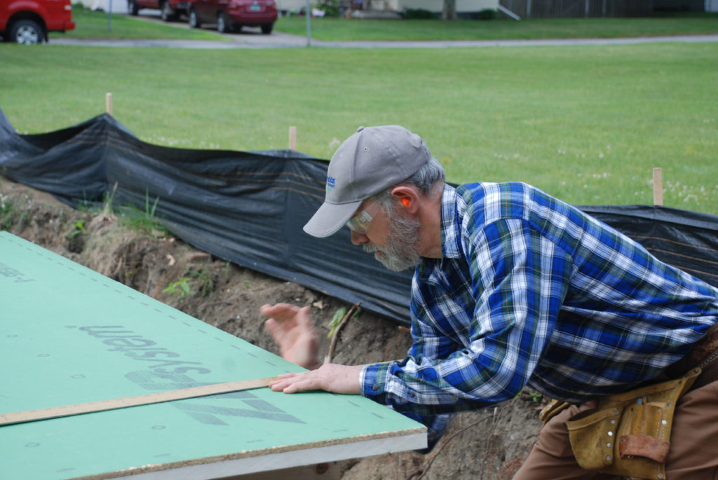 A voluteer measures rigid insultation board at a Green Mountain Habitat for Humanity buildsite