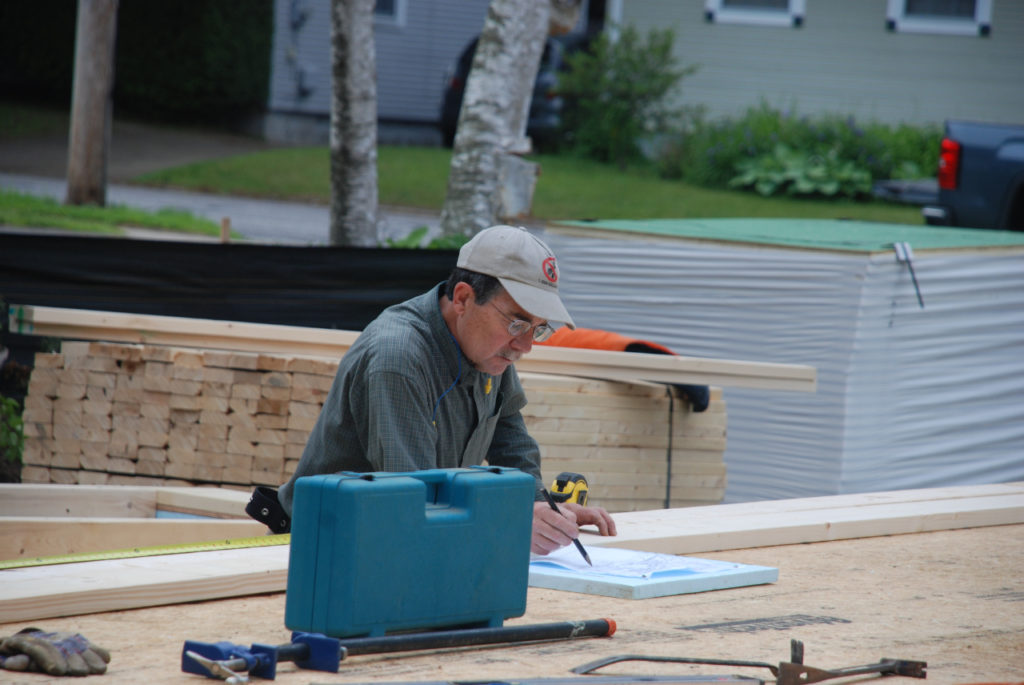 A volunteer consults blueprints at a Green Mountain Habitat for Humanity buildsite