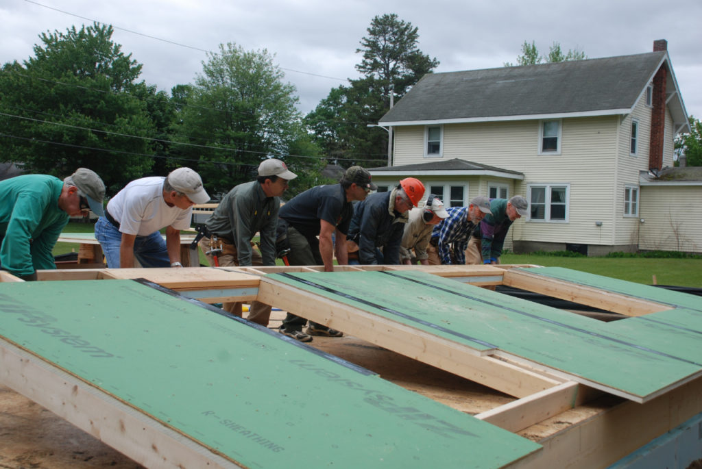 Volunteers work together to erect a wall at a Green Mountain Habitat for Humanity worksite.